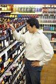 Man taking bottle of wine from supermarket shelf