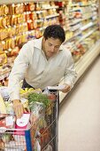Man with shopping list & full shopping trolley in supermarket