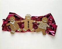 Three Gingerbread Men Resting on Foil Paper