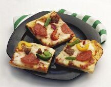 Square Pieces of Pepperoni, Sausage, Pepper and Onion Pizza