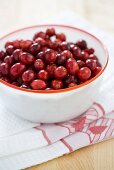 Fresh cranberries in bowl on tea towel