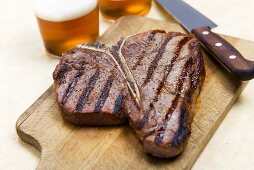 Grilled T-Bone Steak on Cutting Board; Knife and Beer