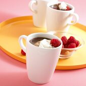 Mugs of Hot Chocolate Topped with Whipped Cream and Raspberries