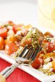 Heirloom Tomato Salad with Pesto Sauce; Fork Stabbing Tomato