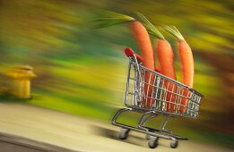 Three carrots in a shopping cart rolling down the street