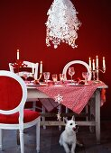 A table laid for Christmas dinner with designer lamps and a dog in the foreground