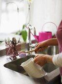 A woman rinsing a white porcelain jug