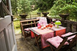 A view onto a laid terrace table with wooden chairs on an old stone patio