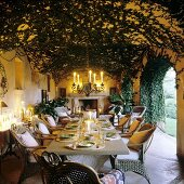 A decoratively laid candle lit table in a foliage-clad arcade