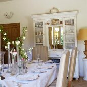 A laid table and a white crockery cabinet with a mirror in a Mediterranean dining room