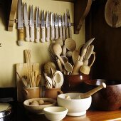 Kitchen implements in container and an assortment of knives on the wall