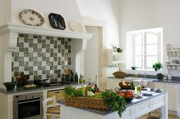 Vegetables on a kitchen table in front of a country house-style oven with an extractor fan