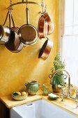 A yellow painted kitchen corner with hanging copper pans and a sink in front of a window