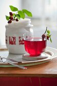 Rosehip tea and a rosehip sprig in a jar