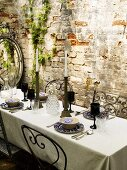 A table in front of a brick wall laid with black wine glasses and candles
