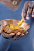 A hand holding a bowl of cornbread sticks