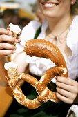 Woman in national dress eating soft pretzel (Oktoberfest, Munich)