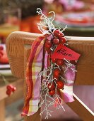 Rose hip decoration with place card on chair back