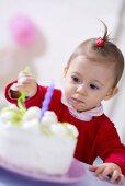 Small girl eating kiwi coconut birthday cake