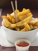 Potato wedges with wooden sticks and ketchup