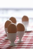 Eggs in eggcups on checked tablecloth