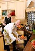 Mann schiebt Ente in den Ofen, dahinter Frau mit Rotweinglas