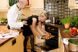 Woman putting duck into oven, man beside her with glass of red wine