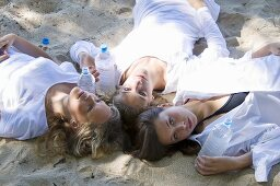 Three girls with bottles of water on sand