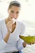 Young woman eating coconut