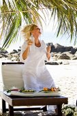 Blond woman drinking mineral water on the beach