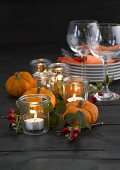 Pumpkins, rose hips, plates, tealights and wine glasses