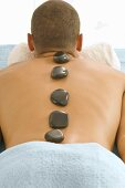 Man with warm stones on his back (Hot stone massage)