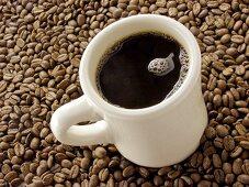 Mug of Black Coffee Resting on Coffee Beans
