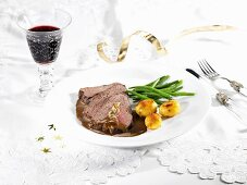 Stuffed roast beef with potatoes and green beans for Christmas dinner