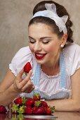 A retro-style girl eating fresh strawberries