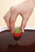 Hand dipped strawberry in chocolate sauce