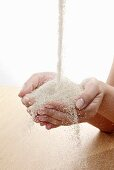 Raw sugar flowing into hands