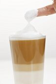 Milk foam covered finger from a glass of Latte Macchiato