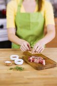 Woman Adding Fresh Herbs to Season a Steak