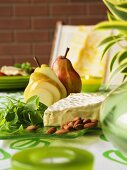 Cheese platter with brie, almonds, baby spinach and pears