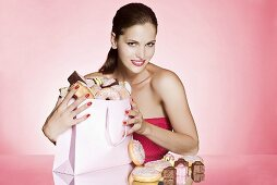 A young woman with bag of cakes and doughnuts
