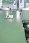 A coffee cup and money on the counter on a diner