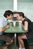 A young couple drinking a milkshake