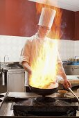 A chef cooking in a commercial kitchen, partially hidden behind a flame