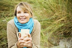 An older woman outdoors with a cup