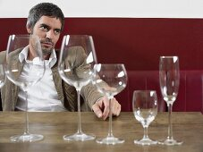 A man sitting at table with various empty wine glasses