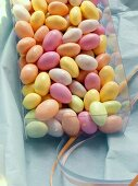 Pastel-coloured sugar eggs (jelly beans) in plastic box