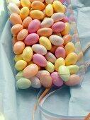 Pastel-coloured sugar eggs (jelly beans) in plastic box