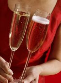 Woman in red dress holding two different champagne glasses