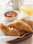Croissants in bread basket, orange marmalade & grapefruit juice